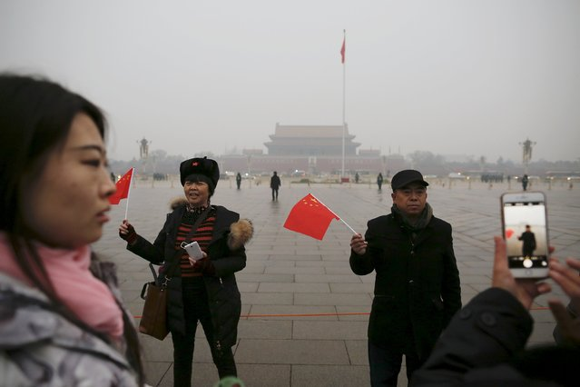 "People with national flags have their picture taken just after a flag-raising ceremony amid heavy smog at Tiananmen Square, after the city issued its first ever ""red alert"" for air pollution, in Beijing December 9, 2015. (Photo by Damir Sagolj/Reuters)"