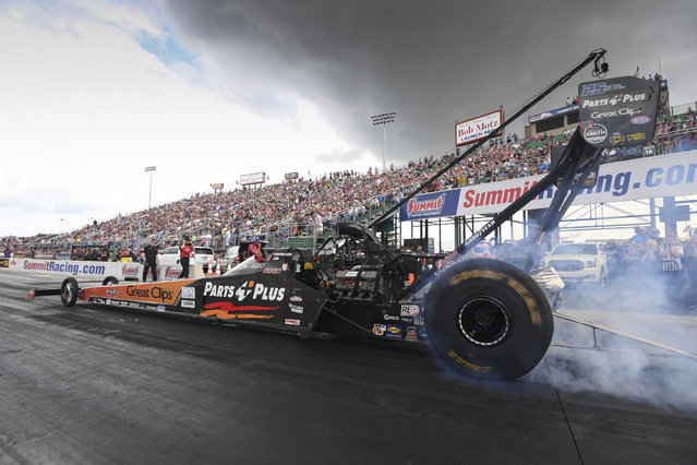 In this photo provided by the NHRA, Clay Millican does a burnout during Top Fuel qualifying Saturday, June 23, 2018, at the 12th annual Summit Racing Equipment NHRA Nationals drag races in Norwalk, Ohio. Millican used a 3.750-second pass at a track record 332.67 mph in the lone qualifying session of the day. (Photo by Jerry Foss/NHRA via AP Photo)