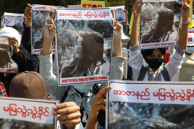 Mandalay University graduates hold posters with an image of Mya Thwate Thwate Khaing, a 19-year old woman shot by police on Feb. 9 in Naypyitaw, during an anti-coup protest in Mandalay, Myanmar, Sunday, February 14, 2021. (Photo by AP Photo/Stringer)