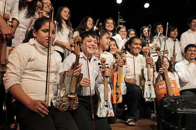 Members of the Orchestra of Recycled Instruments of Cateura pose for the audience during a concert in Asuncion, June 22, 2013. The orchestra is the brainchild of its conductor Favio Chavez, who wanted to help the children of garbage pickers at the local landfill, and the instruments are made from salvaged materials by craftsman Nicolas Gomez. (Photo by Jorge Adorno/Reuters)