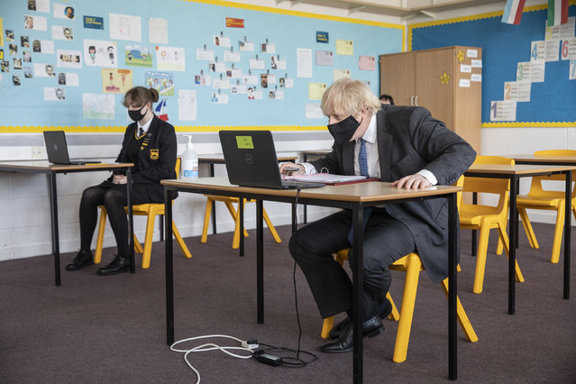 Britain's Prime Minister Boris Johnson takes part in an online class, during a visit to Sedgehill School in Lewisham, south east London, Tuesday, February 23, 2021, to see preparations for students returning to school.  Johnson has announced a gradual easing of one of Europe's strictest lockdowns on, saying children will return to class and people will be able to meet a friend for coffee in a park in two weeks' time. But people longing for a haircut, a restaurant meal or a pint in a pub have almost two months to wait, and people won't be able to hug loved ones that they don't live with until May at the earliest. (Photo by Jack Hill/Pool Photo via AP Photo)