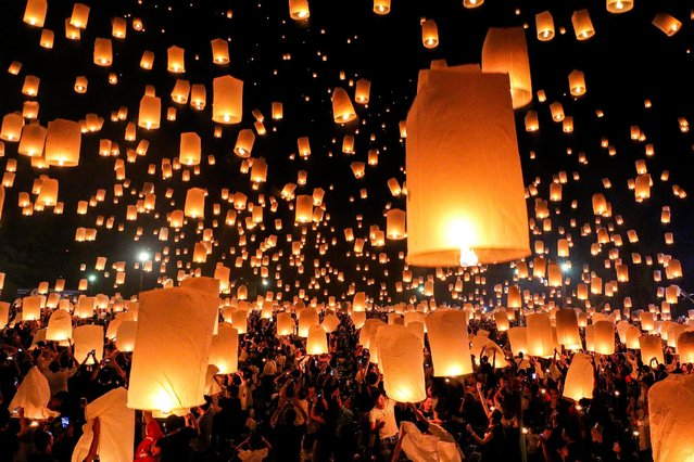 People release floating lanterns during the festival of Yee Peng in the northern capital of Chiang Mai, Thailand November 14, 2016. Yi Peng refers to the full moon day in the second month according to the Lanna lunar calendar (the twelfth month according to the Thai lunar calendar). Swarms of Lanna-style sky lanterns are launched into the air where they resemble large shoals of giant fluorescent jellyfish gracefully floating through the sky. The festival is meant as a time for tham bun, to make merit. Khom loi are made from a thin fabric, such as rice paper, stretched over a bamboo or wire frame, to which a candle or fuel cell is attached. When the fuel cell is lit, the resulting hot air is trapped inside the lantern and creates enough lift for the khom loi to float up into the sky. (Photo by Athit Perawongmetha/Reuters)