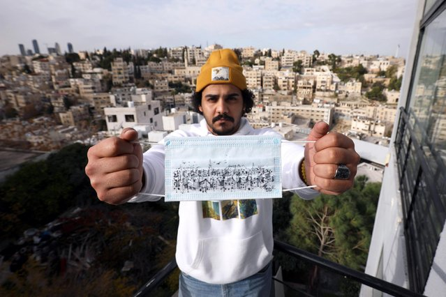 Jordanian artist and architect Saleh Mansour poses with his cityscape sketch on a mask to encourage people to wear them during the COVID-19 pandemic in Amman, Jordan on December 7, 2020. (Photo by Muhammad Hamed/Reuters)