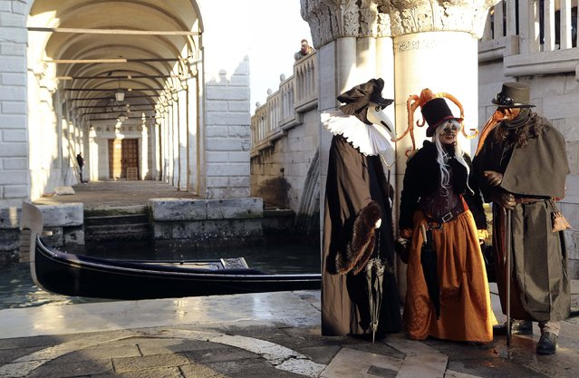Masked revellers pose near a canal next to St. Mark's square during the first day of carnival, in Venice February 1, 2015. (Photo by Stefano Rellandini/Reuters)