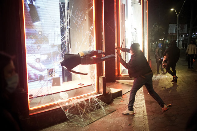 A demonstrator smashes a shop window during a protest condemning the arrest of rap singer Pablo Hasél in Barcelona, Spain, Saturday, February 20, 2021. A fifth night of peaceful protests to denounce the imprisonment of a Spanish rap artist once more devolved into clashes between police and fringe group members who set up street barricades and smashed storefront windows in Barcelona. (Photo by Joan Mateu/AP Photo)