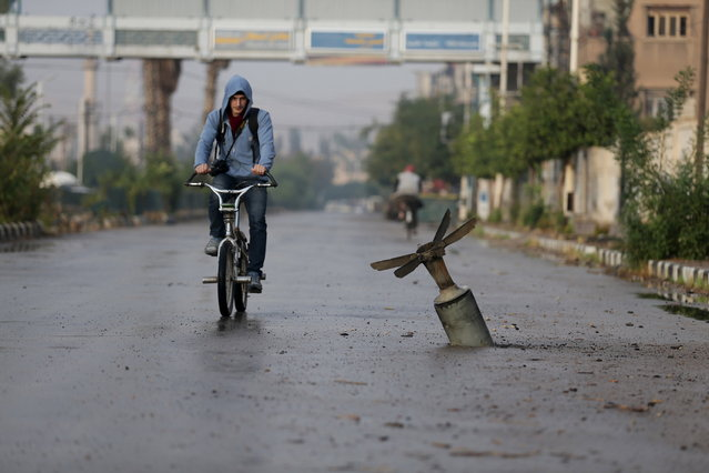 A resident rides his bicycle near what activists said was an exploded cluster bomb shell in the town of Douma, eastern Ghouta in Damascus November 5, 2015. (Photo by Bassam Khabieh/Reuters)
