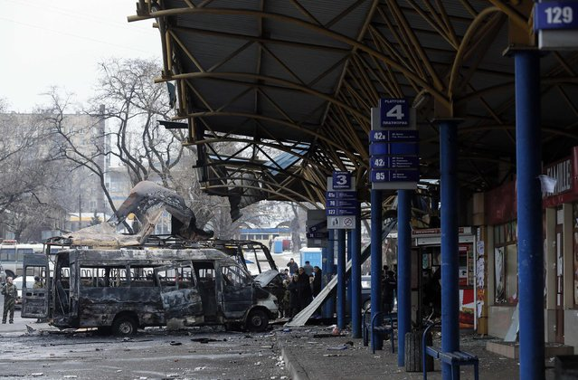 People stand around destroyed vehicles at a bus station after shelling in Donetsk, February 11, 2015. (Photo by Maxim Shemetov/Reuters)