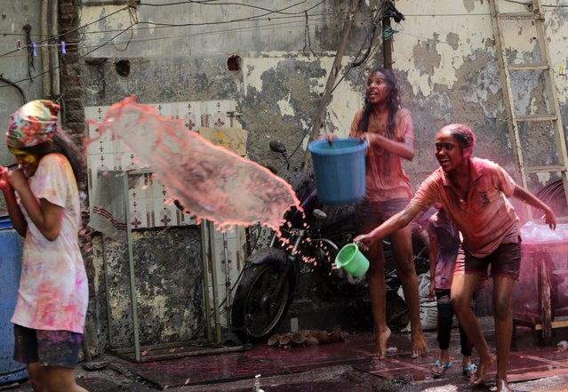 Indian children throw colored water on each other during Holi festival in Mumbai, India, Monday, March 29, 2021. (Photo by Rajanish Kakade/AP Photo)