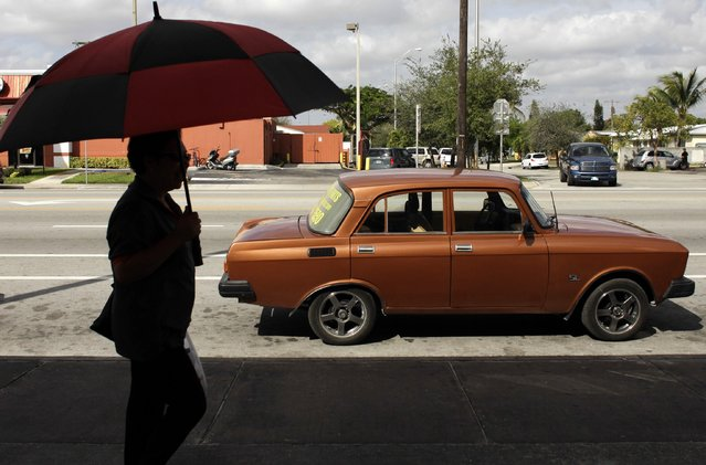 A woman walks past a Moskvich car in front of Fabian Zakharov's Zakharov Auto Parts shop in Hialeah, Florida, February 4, 2015. (Photo by Javier Galeano/Reuters)
