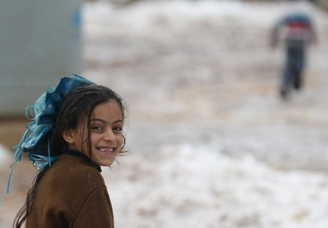 A Syrian girl Mariam from Raqqa looks on as she runs in snow in the Bekaa Valley in Lebanon after the first heavy snow storm hit Lebanon, January 3, 2016. (Photo by Jamal Saidi/Reuters)