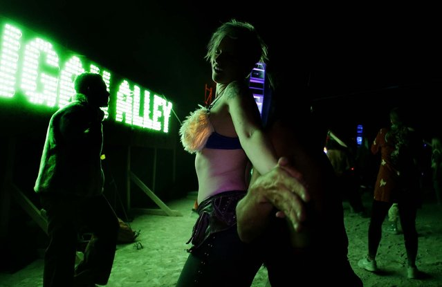 Participants dance during the Burning Man 2013 arts and music festival in the Black Rock Desert of Nevada. (Photo by Jim Urquhart/Reuters)