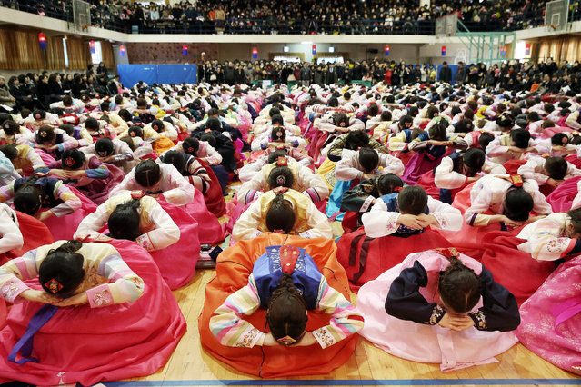 Graduates of Dongmyung Girls High School, all clad in traditional Korean dress (hanbok), bow deeply to teachers and parents during their graduation ceremony at the school in western Seoul, South Korea, 12 February 2015. (Photo by EPA/Yonhap)