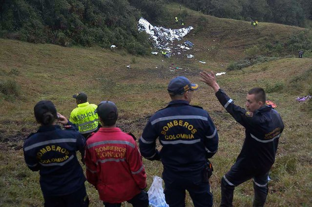 Rescuers gesture near the wreckage of the LAMIA airlines charter plane carrying members of the Chapecoense Real football team that crashed in the mountains of Cerro Gordo, municipality of La Union, on November 29, 2016. (Photo by Raul Arboleda/AFP Photo)