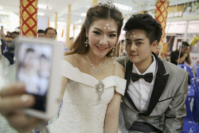 Pichaya Tantip (R) and her partner Phatrnaya Kamploy, a same s*x couple, take pictures of themselves before stepping into a pink coffin during their wedding ceremony at Wat Takien temple in Nonthaburi province, on the outskirts of Bangkok February 14, 2015. (Photo by Damir Sagolj/Reuters)