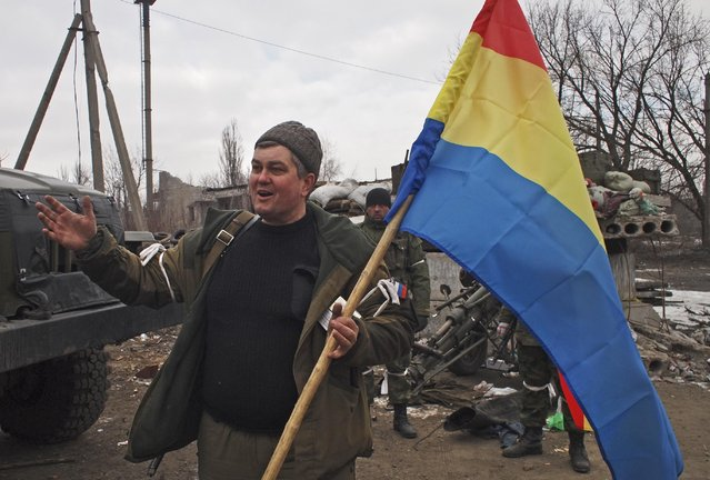 A pro-Russia rebel holds a flag of the rebel-held city of Luhansk in Debaltseve, eastern Ukraine, Thursday, February 19, 2015. (Photo by Peter Leonard/AP Photo)
