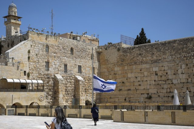 Israel's national flag is lowered to half-mast as the country observes a day of mourning after the death of 45 ultra-Orthodox Jews in a stampede at a religious festival at Mt. Meron last Friday, at the plaza in front of the Western Wall, Judaism's holiest prayer site, in Jerusalem's Old City, Sunday, May 2, 2021. Officials came under growing scrutiny Sunday for ignoring warnings about safety lapses at one of Israel's most visited holy sites, as the country mourned 45 ultra-Orthodox Jews killed in a stampede at a festival there. (Photo by Mahmoud Illean/AP Photo)