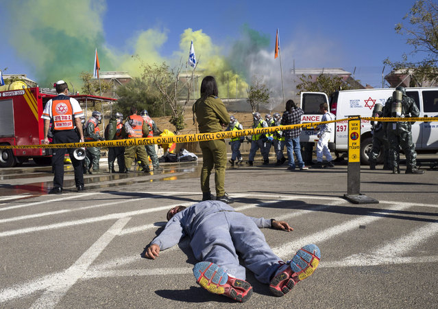 Israeli soldiers play the parts of wounded civilians during a drill simulating a toxic spill from an attack on a train in Beersheba, southern Israel, 13 January 2016, as Home Front medical teams, fire fighters and police carry out rescue operations. The large scale drill is the concluding exercise of the Fourth International Conference on Healthcare System Preparedness and Response to Emergencies and Disasters and includes some 200 of the world's experts on health system readiness from around the world. (Photo by Jim Hollander/EPA)