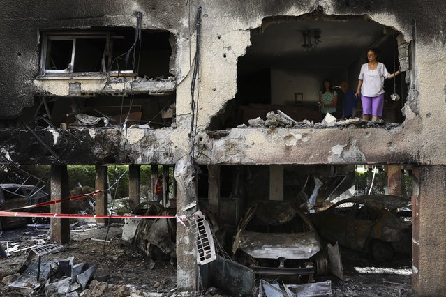 Members of Sror family inspect the damage of their apartment after it was hit by a rocket fired from the Gaza Strip over night in Petah Tikva, central Israel, Thursday, May 13, 2021. (Photo by Oded Balilty/AP Photo)