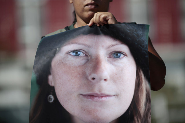 A Greenpeace activist holds a photo of Brazilian Ana Paula Maciel, 31, during a protest in support of activists arrested in Russia, in front of the Russian embassy in Brasilia September 27, 2013. A Russian court ordered 20 Greenpeace activists from around the world to be held in custody for two months pending further investigation over a protest against offshore oil drilling in the Arctic, drawing condemnation and a vow to appeal. Maciel is among the team of activists who are in detention after performing a peaceful protest against oil exploration in the Arctic. (Photo by Ueslei Marcelino/Reuters)
