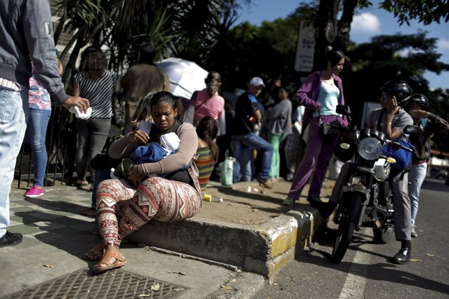 "A woman shields her child from the sun, as she sits in a line to try and buy meat, outside a supermarket in Caracas January 16, 2016. Venezuela's socialist government decreed an ""economic emergency"" on Friday that will expand its powers and published the first data in a year that shows the depth of a recession fueled by low oil prices and a sputtering state-led model. (Photo by Carlos Garcia Rawlins/Reuters)"