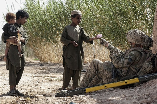 """Soldiers chat to Afghan children during a break in Jamie's picture, """"Flowers for a Friend"""". (Photo by Jamie Peters/PA Wire)"""