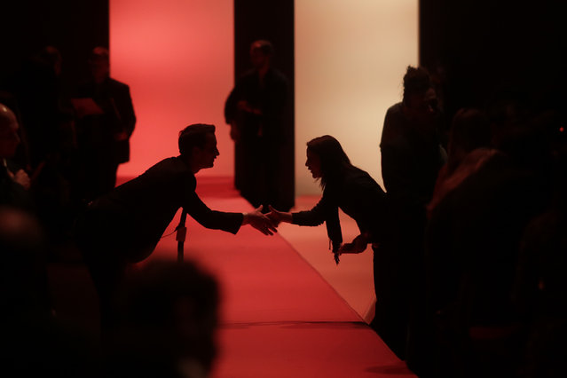 Two visitors shake hands over the runway prior to the fashion show of designer Dorothee Schumacher during theFashion Week in Berlin, Wednesday, January 20, 2016. The Fall/Winter 2016/2017 collections are presented during the Berlin Fashion Week from Jan. 18 to 22. (Photo by Markus Schreiber/AP Photo)