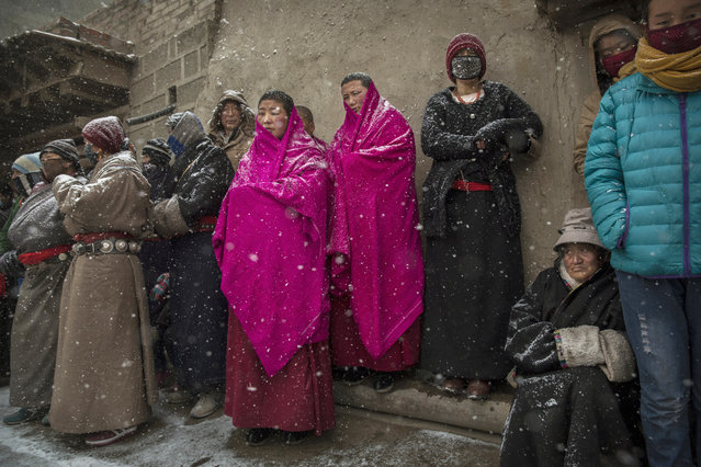 Tibetan Buddhist Nuns of the Gelug, or Yellow Hat order, and worshippers look on at a procession during Monlam or the Great Prayer rituals on March 4, 2015 at the Labrang Monastery, Xiahe County, Amdo, Tibetan Autonomous Prefecture, Gansu Province, China. (Photo by Kevin Frayer/Getty Images)