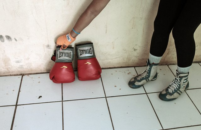 Irene Aguirre, 23, picks up her boxing gloves after training at the National Institute of Sport in Managua March 4, 2015. (Photo by Oswaldo Rivas/Reuters)