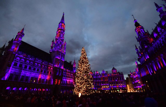 "A Christmas tree stands at the Grand Place (Grote Markt) in Brussels as people gather to watch a sound and light show as part of the ""Winter Wonders"" festivities on November 27, 2016. The new sound and light show at the central square of Brussels includes some 1600 LED lights at the cost of 3,4 million Euros. (Photo by Emmanuel Dunand/AFP Photo)"