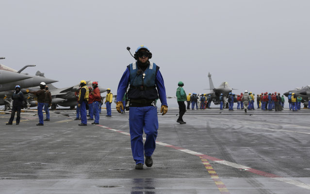 In this Wednesday, March 18, 2015 photo, French sailors work on the flight deck of the French Navy aircraft carrier Charles de Gaulle in the Persian Gulf. (Photo by Hasan Jamali/AP Photo)