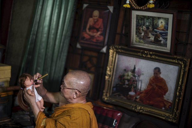 "Buddhist monk Phra Winai Thidtapanyo, 64, anoints on a ""child angel"" doll during a blessing ritual at Wat Bua Khwan temple in Nonthaburi, Thailand, January 26, 2016. (Photo by Athit Perawongmetha/Reuters)"