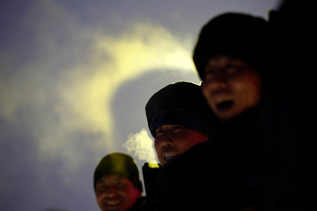 Workers smile under an ice sculpture for the upcoming Harbin International Ice and Snow Sculpture Festival, in Harbin, Heilongjiang province, China, December 19, 2016. (Photo by Aly Song/Reuters)