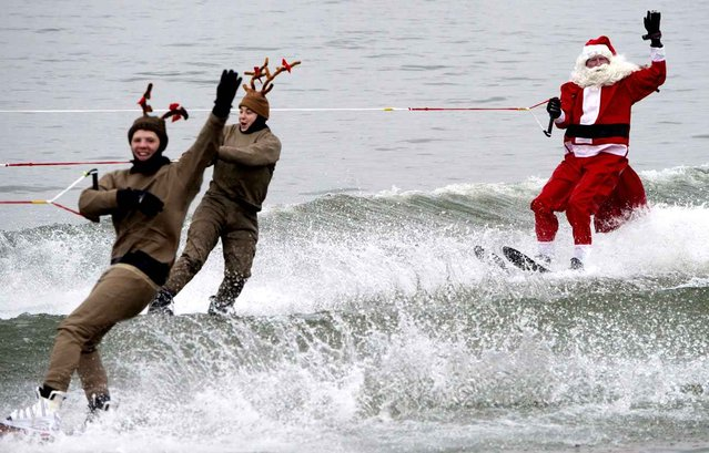 Members of the volunteer Water Skiing Christmas Show, including a water skiing Santa Claus with elves, reindeer, the Grinch, and others, water ski December 24, 2016, on the Potomac River, in Alexandria, Virginia, just down the river from Washington, DC. (Photo by Paul J. Richards/AFP Photo)