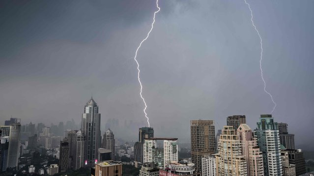 Lightning bolts strike buildings during a thunderstorm in Bangkok on May 3, 2021. (Photo by Mladen Antonov/AFP Photo)