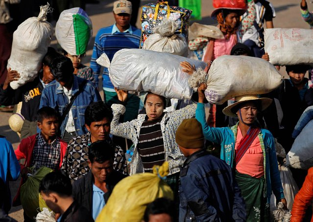 Migrant workers who fled from Karmine get ready to board a vehicle to return home, at a temporary refugee camp in a monastery in Lashio February 21, 2015. (Photo by Soe Zeya Tun/Reuters)