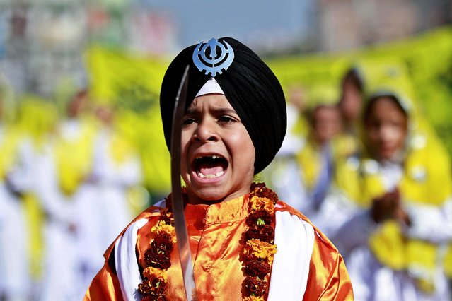 A young Sikh boy shouts religious slogans during a procession ahead of the birth anniversary of Guru Nanak in Jammu, India, Wednesday, November 21, 2018. The birth anniversary of Guru Nanak, founder of Sikhism and first Sikh guru, will be marked on Nov. 23. (Photo by Channi Anand/AP Photo)