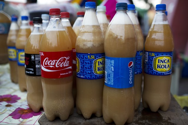 In this Sunday, March 29, 2015 photo, bottles of chicha, a popular fermented corn drink, are displayed for sale on a street stand, outside the Acho bullring, the venue for the Vencedores de Ayacucho dance festival, in the Acho bullring in Lima, Peru. The semi-sweet tasting alcoholic drink is sold in recycled plastic soft drink bottles, for about the equivalent of three U.S. dollars per bottle. (Photo by Rodrigo Abd/AP Photo)