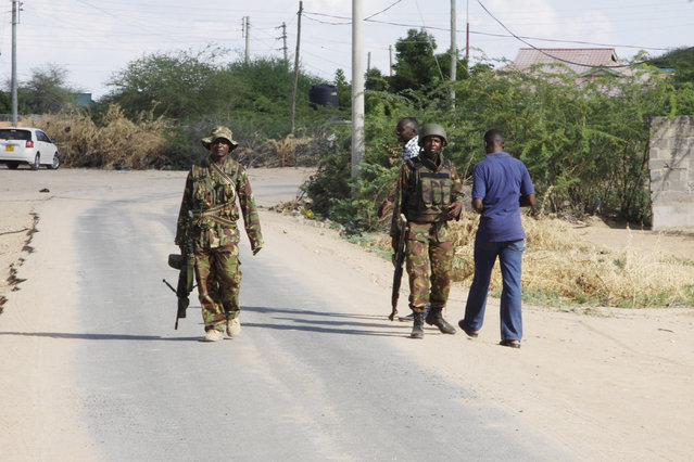 Members of Kenya's Defence Forces secure the area of the Garissa University college, in Garissa, Kenya, Thursday, April 2, 2015. Witnesses say the gunmen who stormed a college in Kenya this morning identified themselves as members of al-Shabab, the Islamic extremist group from neighboring Somalia. A mortuary attendant in the town of Garissa says at least 15 people have been killed in the attack and 60 injured. (Photo by Khalil Senosi/AP Photo)