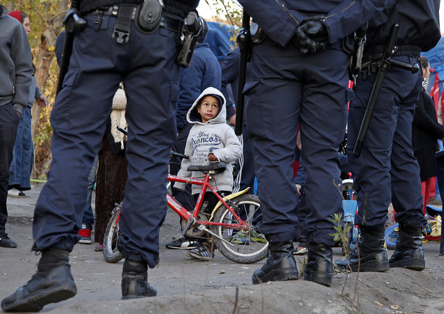 A Roma child looks at French police standing guard as Roma families are evacuated from their illegal camp near the Var river in Nice, southeastern France, November 27, 2013. (Photo by Eric Gaillard/Reuters)