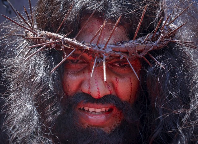 A penitent, dressed as Jesus Christ, reacts as he carries a cross during a ritual to mark Good Friday in Mumbai April 3, 2015. (Photo by Shailesh Andrade/Reuters)