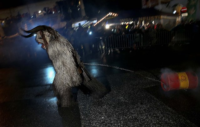 A participant dressed as the Krampus creature pulls a barrel of fire past onlookers during his search for delinquent children in Neustift im Stubaital. (Photo by Sean Gallup)