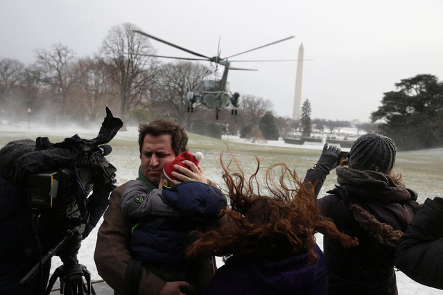 A man holds his child as Marine One blows up a cloud of snow as U.S. President Barack Obama departs the White House in Washington, U.S., January 7, 2017. (Photo by Joshua Roberts/Reuters)