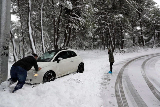 A man pushes a car from the snow after his driver lost control, in Malakasa about 29 kilometers (24 miles) north of Athens on Tuesday, January 10, 2017. Snow closed schools in the capital, as added pressure on the government to speed up winter preparations for thousands of refugees living in camps around the country. (Photo by Thanassis Stavrakis/AP Photo)
