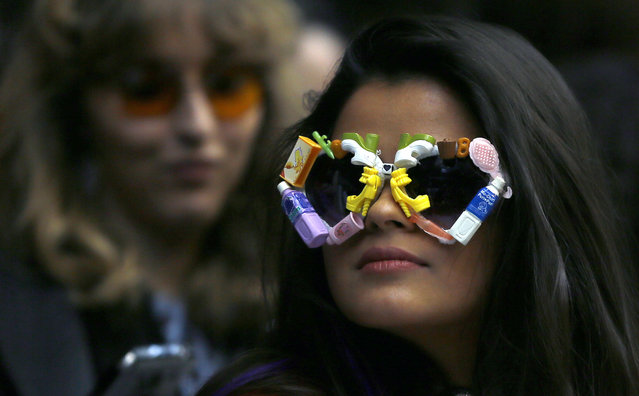 A guest wearing colorful glasses watches the Ryan LO Autumn/Winter show at London Fashion Week, Friday, February 19, 2016. (Photo by Kirsty Wigglesworth/AP Photo)