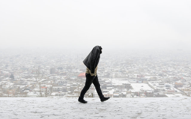 A man covers his head walks on a hilltop on a snowy day in Kabul, Afghanistan January 14, 2017. (Photo by Mohammad Ismail/Reuters)