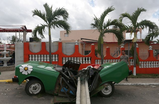 A man looks at a car hit by a post after a tornado ripped through a neighbourhood in Havana, Cuba on January 28, 2019. (Photo by Fernando Medina/Reuters)