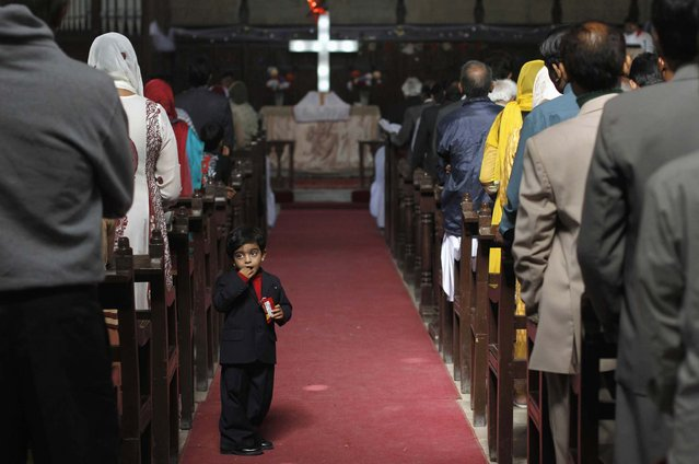 A Pakistani Christian boy eats snacks as he attends mass along with others on Christmas day at St Andrew's Church in Karachi December 25, 2013. (Photo by Athar Hussain/Reuters)