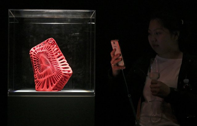 A woman takes a picture of the 3D printed shoes by Mexican architect Fernando Romero's during the Milan Design Week, April 16, 2015. (Photo by Stefano Rellandini/Reuters)