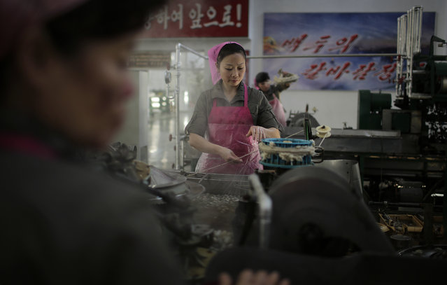 In this Friday, January 6, 2017, photo, North Korean women boil silkworm cocoons at the Kim Jong Suk Silk Mill in Pyongyang, North Korea. (Photo by Wong Maye-E/AP Photo)