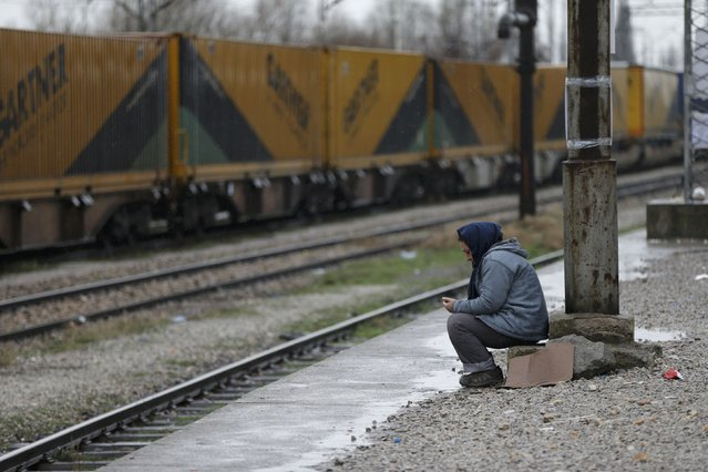 A migrant woman from Afghanistan sits at the Macedonian-Serbian border near the village of Tabanovce, Macedonia February 24, 2016. (Photo by Marko Djurica/Reuters)